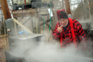 Dressed as Paul Bunyan, Ron Johnson, Breezy Point, tastes the maple syrup he tapped and processed for many years.