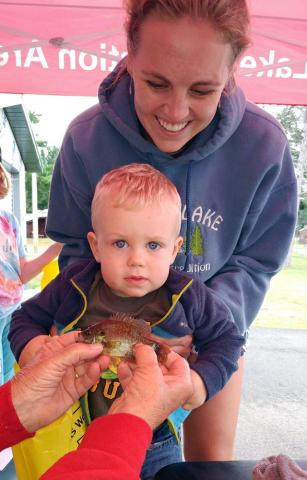 Fishing Derby contestant, 1-year-old Luke Reineke with his fish at the weigh-in. - photo submitted.